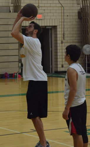 T-L Photo/SETH STASKEY FORMER ST. Clairsville standout and current two-sport athlete at West Liberty University Dan Monteroso demonstrates a shooting drill for camper David Zwack at the annual St. John Central Basketball Camp on Thursday.