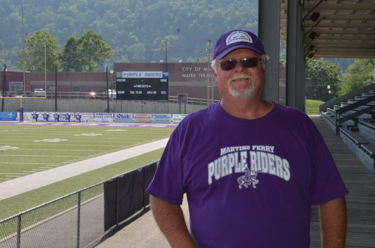 T-L Photo/RICK THORP  FRED BECK enjoys a moment at Purple Rider Stadium with the scoreboard in the background. Beck, a 1972 Martins Ferry High grad, has been operating the scoreboard for nearly 40 years.