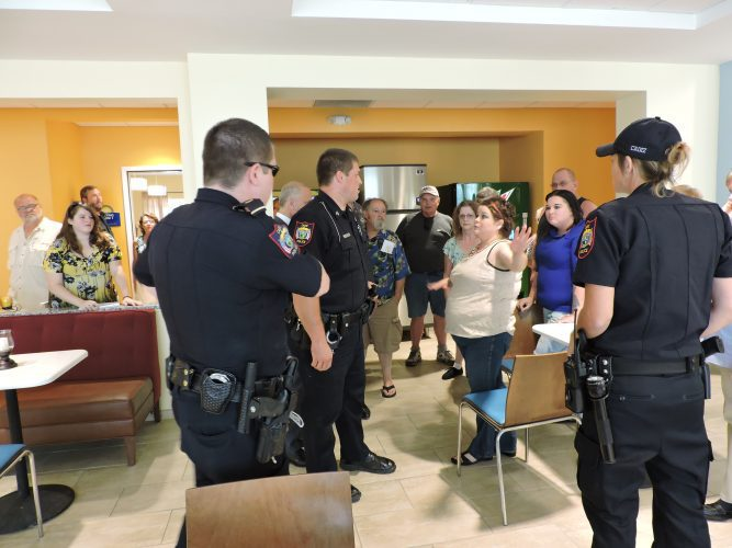T-L Photo/SHELLEY HANSON SCIO RESIDENT Trish McAfee, center, talks to Cadiz police before being arrested on Wednesday at the Days Inn in Cadiz, where she organized a meeting about Scio's water problems.
