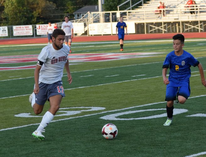 T-L Photo/SETH STASKEY ST. CLAIRSVILLE senior Jordan Vincent dribbles the ball up the field during Thursday's game against Philo at Red Devil Stadium. Vincent scored twice, but  the Red Devils fell to the Electrics, 3-2.