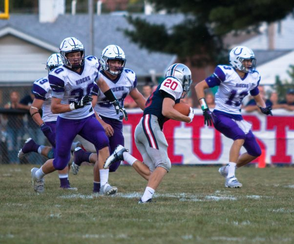 BUCKEYE LOCAL running back John Marelli is chased down by Martins Ferry defenders Logan Selby (30), Dalton Hoover (34) and Corey Bennett (19) during Friday's game in Yorkville. The Purple Riders rolled to a 74-0 victory.