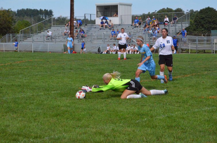 T-L Photo/KIM NORTH HARRISON CENTRAL goalkeeper Ashley Mencer dives to make a save Saturday morning during the Huskies' 3-2 loss to Oak Glen at Dr. James Z. Scott Memorial Field in Scio. She finished with 11 saves. The Golden Bears' Natalie Szpyrka (4) and the Huskies' Taylor Easlick (29) look on.