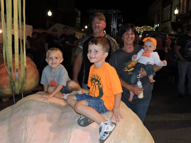 T-L Photo/JENNIFER COMPSTON-STROUGH - Todd and Donna Skinner of Barnesville, growers of this year's 1,739-pound King Pumpkin, smile as their grandchildren climb atop the winning entry while it sits on the scale in downtown Barnesville on Wednesday. Seated on the gourd are Brogan Shilling, left, and Bryar Shilling, while Donna holds granddaughter Remmy Skinner.