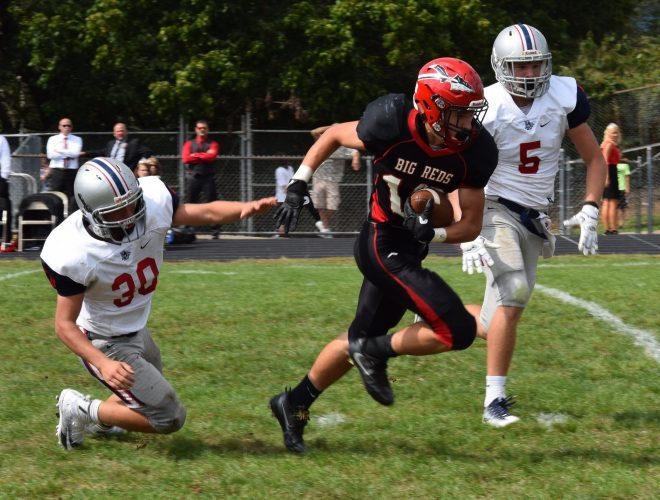 BELLAIRE RUNNING back Tyson Camsky rips through the Buckeye Local defense en route to a touchdown Saturday afternoon at Nelson Field. Pictured for the Panthers are Jack Reese (30) and Sean Millard (5). The Big Reds made it three wins in a row with a 62-7 victory.