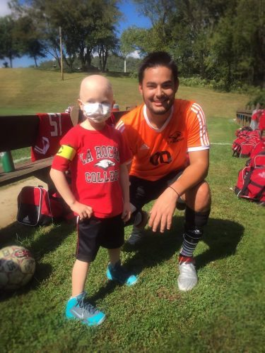 Photo Provided MARTINS FERRY kindergartner Leo Zambori poses with La Roche College soccer player Conner Hagins prior to a match last week at Bethany College. Zambori served as an honorary captain for the match because of a relationship he formed with Hagins during a hospital stay in Pittsburgh. Zambori is currently battling leukemia.