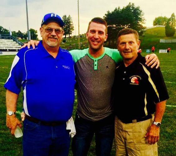 Photo Provided CASEY TOLZDA, middle, who served as the public address voice of the recent Rally for Life flag football game between Beallsville and Woodsfield/Monroe Central alumni, meets with the game's head coaches — Paul Kanzigg, left, and Jay Circosta.