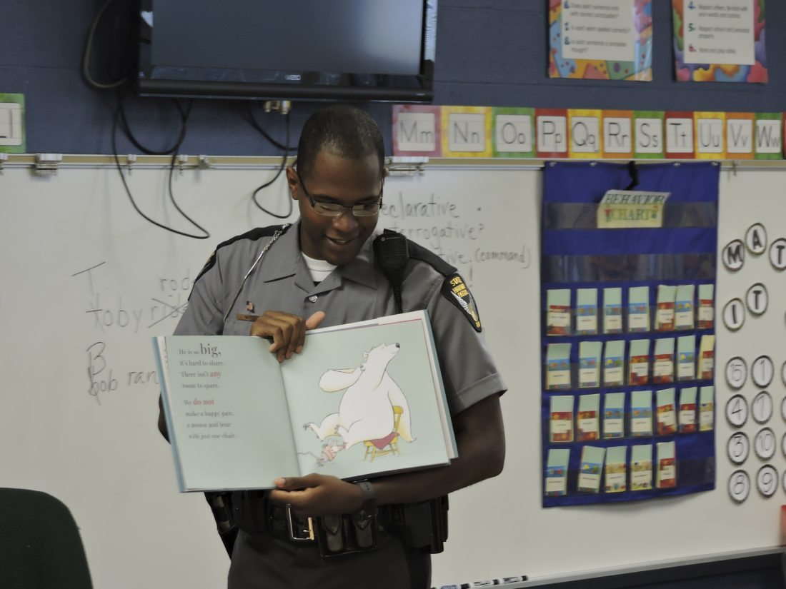T-L Photo/DYLAN McKENZIE  Chase Watts of the Ohio State Highway Patrol reads to a group of students at Ayers Elementary School. Watts is the creator of the Books with Badges reading program.