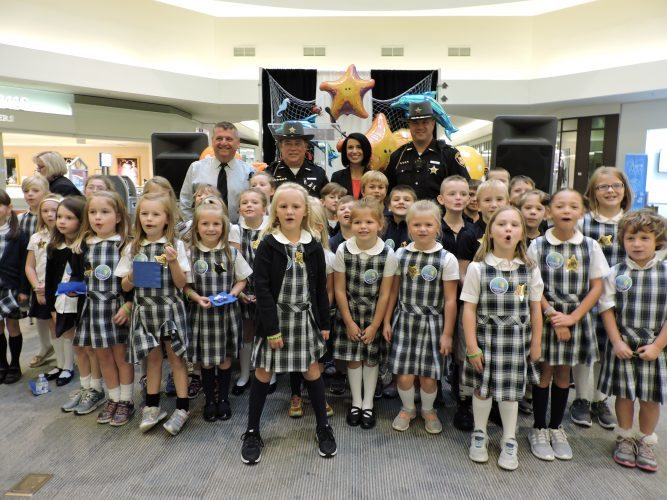 T-L Photo/JANELL HUNTER First and second grade students from Our Lady of Peace School pose with Belmont County Commissioners Mark Thomas (back row, from left), Belmont County Sheriff Dave Lucas, Commissioner Ginny Favede and Chief Deputy James Zusack at an anti-bullying event at the Ohio Valley Mall on Thursday.