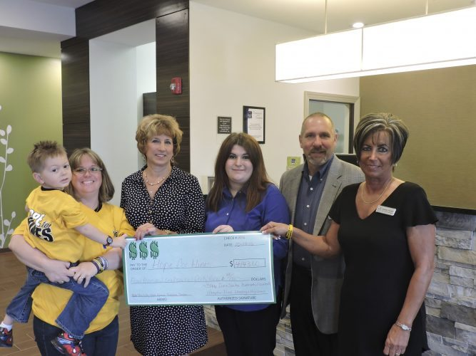 T-L Photos/DYLAN McKENZIE  Hines Rotriga, left, and his mother, Debbie, accept a check from the hotel staff members who raised money for their family to help cover Hines' medical expenses. With them, from left are Jodie Grubler from the Sleep Inn at Moundsville; Emily Wensyel from the Hampton Inn at The Highlands; Jerry Delman, general manager, and Debbie Fisher, assistant general manager, of the Sleep Inn at Belmont.