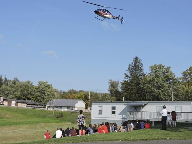 Students at East Richland Christian School look to the sky as an Air Evac helicopter comes in for a landing.