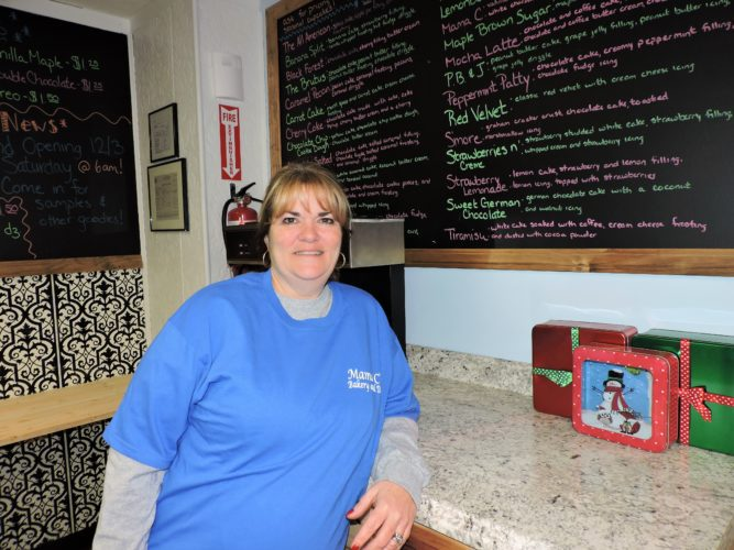 T-L Photo/SHELLEY HANSON PRISCILLA CIONNI stands in front of the cupcake menu board at the new Mama C's Bakery & Deli on Fifth Street in Martins Ferry. The bakery held a soft opening this morning and is having a grand opening on Saturday with free samples.