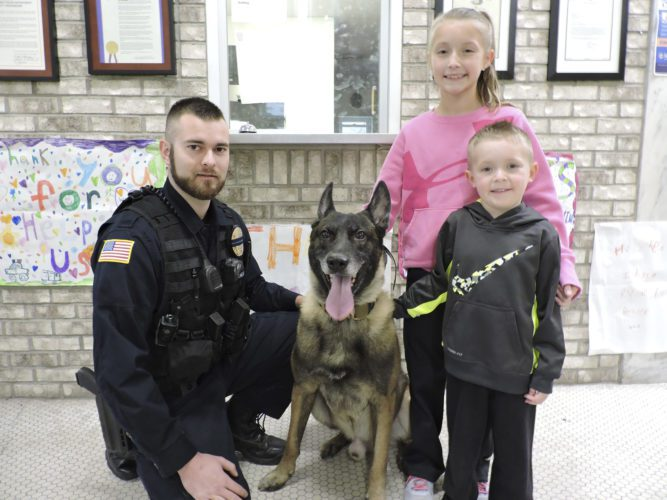 T-L Photo/JANELL HUNTER John Holmes, K-9 officer with the Martins Ferry Police Department, poses with his K-9 partner, Ecko, and two residents of Martins Ferry, Lakyn Call, standing, and Kade Call.