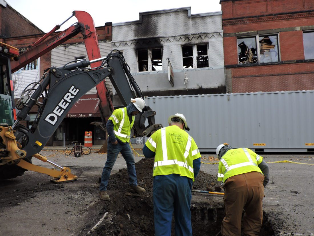 T-L Photos/SHELLEY HANSON EMPLOYEES with Columbia Gas, from left, Ean Rizor, Jim LaRoche and Orville Smith work to shut off natural gas lines near the Fourth Street demolition site in Martins Ferry on Friday.