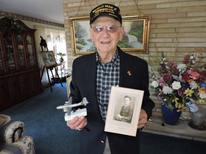 T-L Photo/SHELLEY HANSON DR. ROME Raimonde of Martins Ferry holds a photo of himself when he served in the military during World War II. He also holds a model of a B-29 bomber.