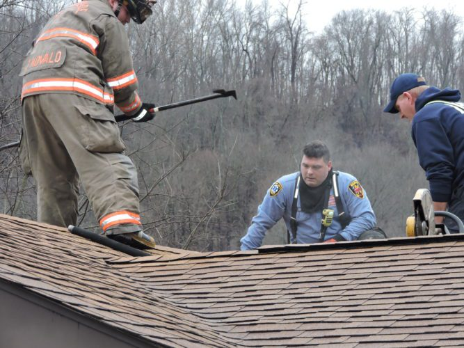 T-L Photo/SHELLEY HANSON  OR&W Fire District firefighter Jay Kovalo, left, today digs into the roof of a Shaver Hill Road home's garage roof with a pick axe as Capt. Robert Conaway and Chris Brokaw, both with the Neffs Volunteer Fire Department, assist.