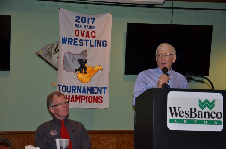 T-L Photo/KIM NORTH RON MAUCK, for whom the Ohio Valley Athletic Conference Wrestling Tournament is named, speaks to conference coaches and members of the media during Monday night's press conference inside WesBanco Arena. The gigantic three-day event unfolds Thursday at the downtown Wheeling facility, with the championship finals scheduled for Saturday at 6:30 p.m. Looking on is tournament director Dr. Dan Doyle.