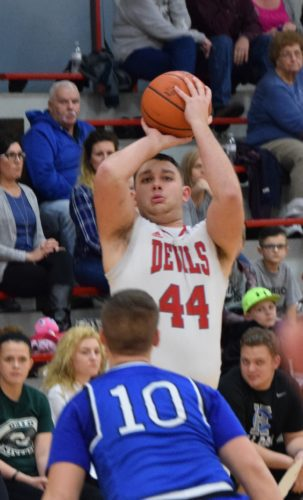 ST. CLAIRSVILLE senior Michael Scarnecchia goes up for a shot over Harrison Central's Jacob Barr during Tuesday's game. Scarnecchia scored his 1,000th career point in the second half and helped spark the Devils to a 63-47 victory.