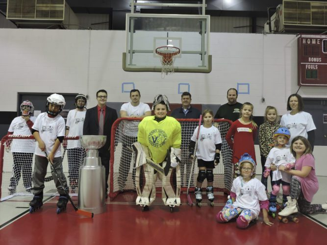 T-L Photo/DYLAN McKENZIE  Coaches and players in the St. Clairsville Co-ed Roller Hockey League pose for a group picture at a practice session Wednesday. From left are Robert Wensyel, Marius Trouten, Tommy Wensyel, Badyn Woodford,  coach Tom Wensyel, Ashton Glover, coach Doug Glover, Abby Brocklehurst, Rec Center program supervisor Sean Hanley, Elissa Goudy, Elanna Goudy, Kari Wensyel, Kiara Wensyel (kneeling), Cecelia Wensyel and Madison Samuels.