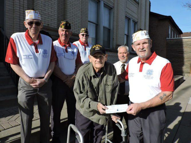 T-L Photo/JANELL HUNTER Martins Ferry resident and Vietnam War veteran John Burch, front left, receives a $1,500 donation from Bellaire VFW Post 626 to help with living expenses. Handing him the check is post Commander Terry Wildman. Behind them, from left, are post Quartermaster Harold Carman, Chaplain Jim Weekley, House Committee member Tom Cottello and Martins Ferry Mayor Robert Krajnyak.