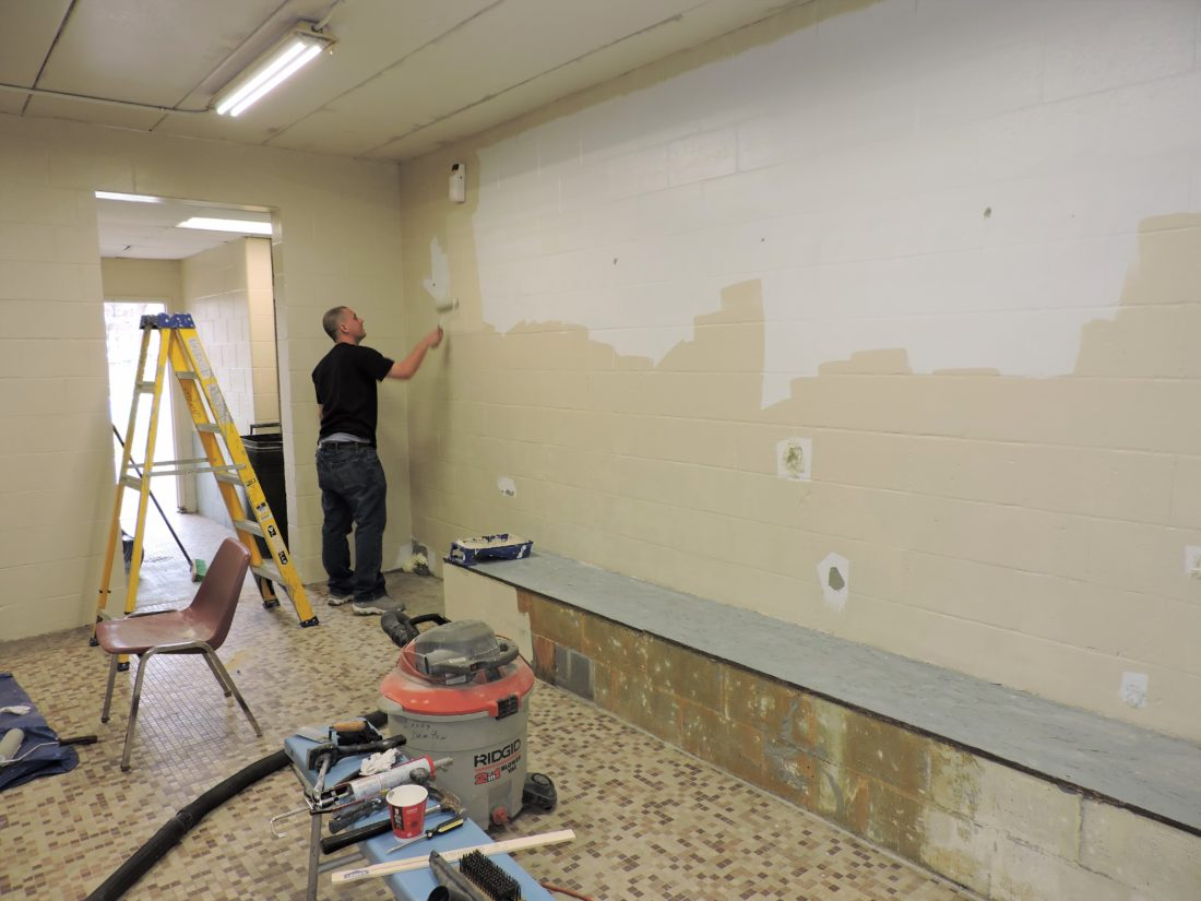 T-L Photo/SHELLEY HANSON VOLUNTEER JOHN Bennington rolls on a new coat of paint inside a locker room at the Martins Ferry Recreation Center on Tuesday. The center is getting ready for summer swimming season.