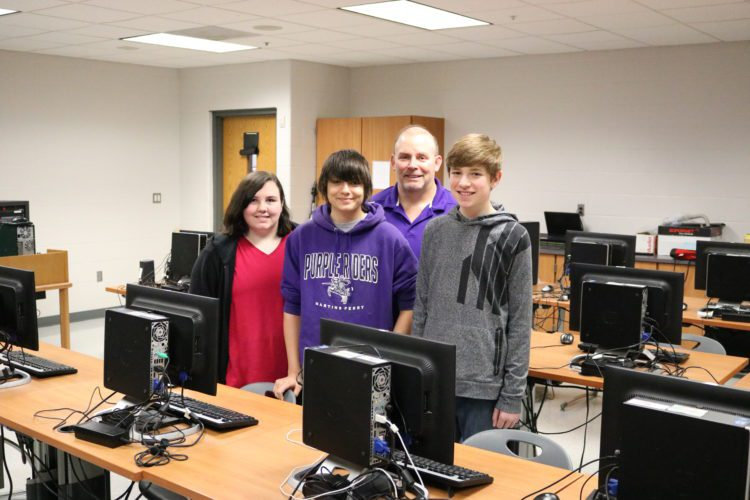 Photos Provided  Martins Ferry Middle School students Kameron Myers, Skyler Sall, and Makenna Klarr stand with teacher Greg Steele for a picture celebrating their winning of the  National Education  Foundation's Minecraft Contest. The contest tested students digital literacy by having them create items in Minecraft that represent school spirit.