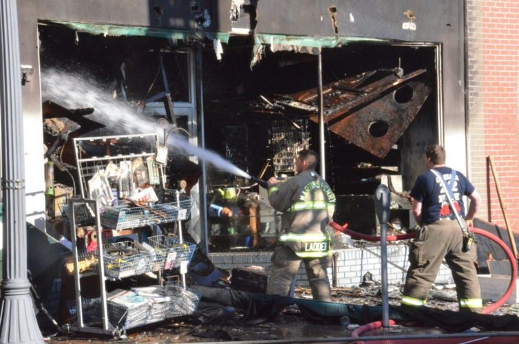 File photo MARTINS FERRY volunteer firefighters work on hot spots smoldering following a devastating Oct. 9 fire in downtown Martins Ferry that destroyed several businesses including Winter's Hardware store, shown here.