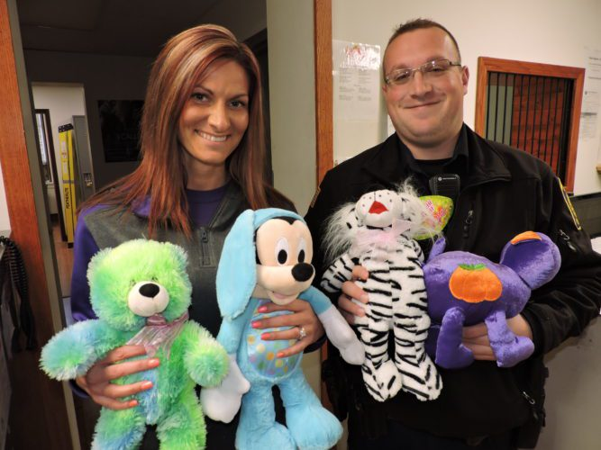 T-L Photo/SHELLEY HANSON MARTINS FERRY Police Department Dispatcher Amber Ferguson, left, and Officer Jon Young hold stuffed animals donated to the department last year. A toy drive to add to that collection is being held Thursday at The Times Leader's office, 200 S. Fourth St., Martins Ferry.