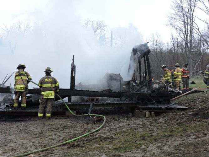 T-L Photo/JENNIFER COMPSTON-STROUGH Firefighters work to douse hot spots after a fire destroyed a home just outside Mount Pleasant on Tuesday afternoon. The family, including twin 5-year-old boys, lost everything in the blaze.