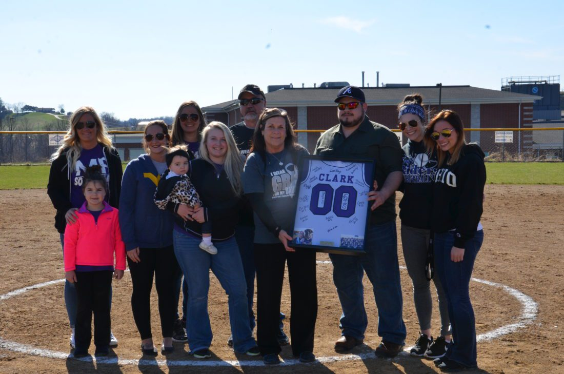 MARTINS FERRY High School retired the No. 00 softball jersey worn by former player Kylie Clark on Wednesday afternoon during pre-game ceremonies high atop the Purple City. From left are former teammates and Clark's parents and brother Kylie Stalder, Ava Suriano, Beth Hotlosz, Sis Frohnapfel, Cassie Hanson holding Ryleigh, Bruce Clark, Kim Clark, Shane Clark, Shayla Outward and Addie Suriano.  T-L Photo/ KIM NORTH
