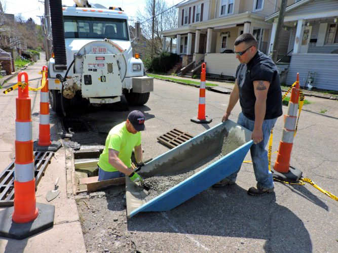 T-L Photos/SHELLEY HANSON MARTINS FERRY city worker Cody Engleman, right, holds a bin of fresh concrete mix being used by worker Mike Reese, left, to fix a storm drain lid on Monday afternoon.