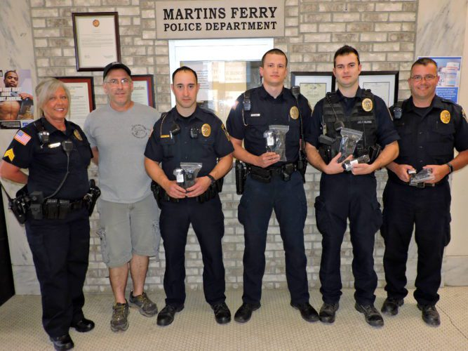 T-L Photo/SHELLEY HANSON RON NAYLOR, second from left, of Fat Boys Bail Bonding donates tourniquets to the Martins Ferry Police Department on Friday. From left are Sgt. Beth Scales, Naylor, Officer Steve Veltri, Officer Shamus Nixon, Officer John Holmes and Sgt. Bob Walton hold some of the tourniquets given to them.