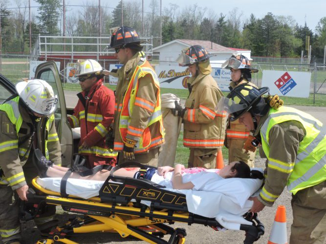 T-L Photo/ ROBERT A. DEFRANK Students at Union Local High school observe a mock crash and emergency response Thursday. Area emergency response agencies arrived and enacted standard treatment of multiple critical injuries and a fatality. Faculty and participants hope that observing a scenario that involves their friends in this situation will dissuade students from making poor choices during the prom.