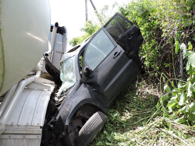 T-L Photo/JANELL HUNTER An SUV is pinned against an embankment by a tractor-trailer hauling 80,000 pounds of sand following a crash at Ohio 7 and Hanover Street in Martins Ferry on Friday.