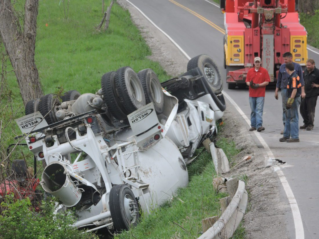 T-L Photo/ ROBERT A. DEFRANK A cement truck rests on its roof after it overturned on a curve while traveling south on Ohio 26 near Bethesda. No one was injured, but the driver was flown to a Pittsburgh hospital with non-life-threatening injuries.