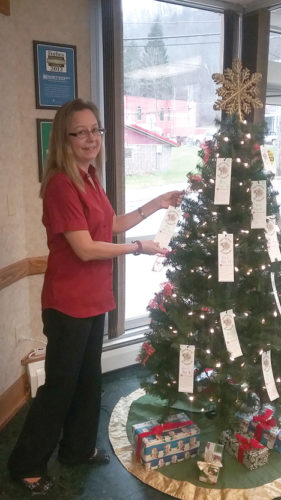 Tags are on the Christmas Tree at Northwest Bank in Tidioute. Feel free to select a tag/tags and shop for the child. Suggestions are on the tags for the children. Have the unwrapped items back to the bank by Dec. 14. Pictured is Lisa Imperial of Northwest Bank placing tags on the tree.