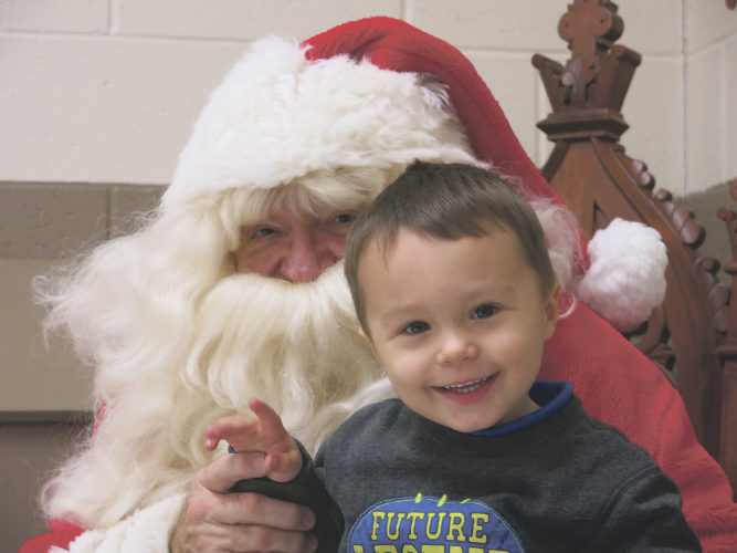Times Observer photo by Stacey Gross Richard Tompson was Santa for the evening. Raymond Yoder, 3, enjoyed visiting with him. He hopes Santa has a tractor for him on Christmas morning. He also loves the cookies and candy that come along with the holiday, and his elf on the shelf, named Lucky Jingleburg.