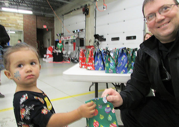Photos submitted to Times Observer Amaya Cradduck receives a goodies bag from Chief Todd Mineweaser, at the Youngsville Hometown Christmas.