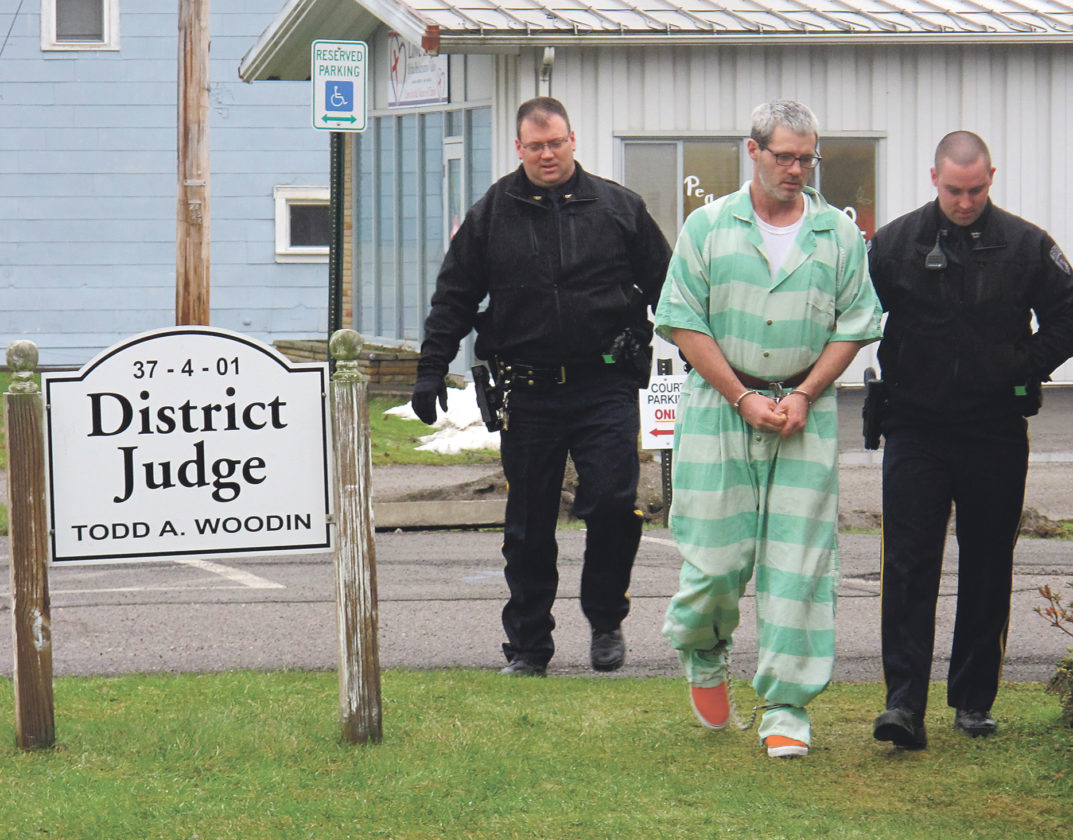 Times Observer photo by Brian Ferry Youngsville Chief of Police Todd Mineweaser, left, and Officer Ben Leach, right, escort Jamie Crick to District Justice Todd Woodin's office on Wednesday afternoon.