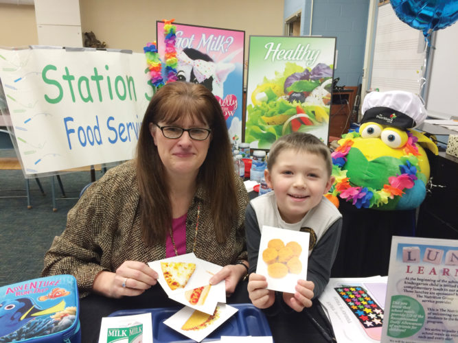 Bryson Hurley, future EES Knight, stops at The Nutrition Group table during EES Kindergarten registration to learn all about building a good lunch from Assistant Food Service Director, Candy Rieder.
