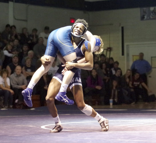 Times Observer photo by Ben Oviatt Warren's Alex Weston lifts Eisenhower's Sam Holt off the mat during their 132-pound match Friday at Warren Area High School. Weston ended up winning via pinfall in overtime to help the Dragons pull out a 42-27 team victory.
