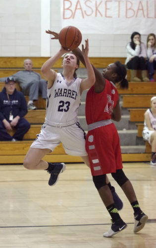 Warren senior Megan Wortman (23) draws a foul during the second half of her team's 69-50 win over East Monday at Warren Area High School.
