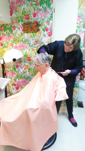 Times Observer photo by Stacey Gross Mary Ann Kuzmin gives a haircut to Ted Bogdon at the Hospice House in Warren.