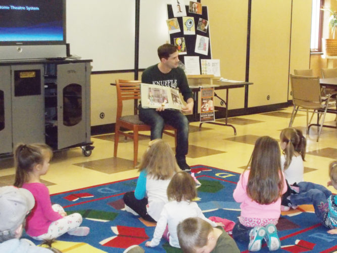 Photo submitted to Times Observer Zach Robertson reads Knuffle Bunny: a Cautionary Tale by Mo Willems to children during the Warren Public Library's A Pigeon, A Knuffle Bunny and Some Pizza program. Children and their families enjoyed several stories about Mo Willem's beloved Pigeon, Trixie and Knuffle Bunny characters. There was also pizza and coloring sheets for all and some lucky children won door prizes. This program was offered in honor of the Knuffle Bunny play,  which will be presented by the Warren Players at the Struthers Library Theatre at 7 p.m. February 23-25, and at 2 p.m. on February 26.  Mr. Robertson plays the role of Knuffle Bunny in this whimsical production, which only lasts an hour, just the right fit for younger children. Contact the Struthers Library Theatre with any questions.