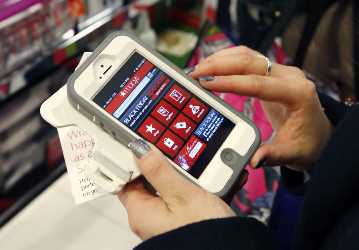 AP PHOTO In this Nov. 23, 2012, file photo, Tashalee Rodriguez, of Boston, uses a smartphone app while shopping at Macy's in downtown Boston.