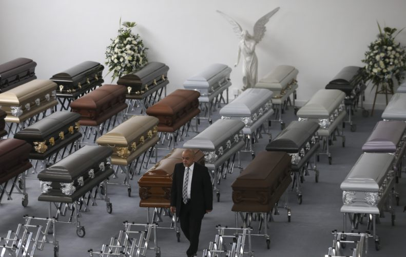 AP PHOTO A funeral employee walks past coffins containing the remains of the victims of the Colombian air tragedy are lined up in the parking garage of the San Vicente funeral home in Medellin, Colombia, Thursday. Because of the large number of casualties, the funeral home had to place the coffins in its parking garage. Forensic authorities say they have managed to identify a majority of the victims of Monday's crash and hope to finish their work on Thursday.