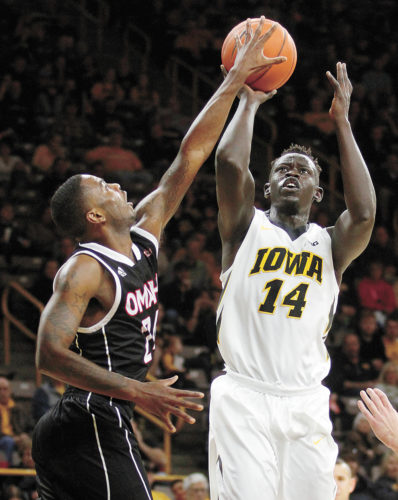 AP PHOTO • Iowa's Peter Jok (14) takes a shot in front of Omaha's Tra-Deon Hollins during the second half of a college basketball game on Saturday in Iowa City.