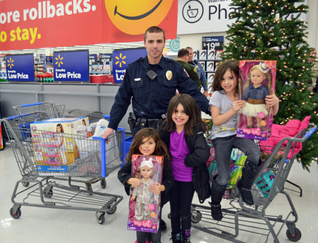 T-R PHOTO BY SARA JORDAN-HEINTZ The Gohring sisters were invited to participate in the Shop With a Cop program after MPD Officer Dane Bowermaster (pictured) responded to a burglary at their home on Black Friday. All of the family's electronics and Christmas presents were stolen. However, the sisters each got to shop with a cop to replace some of their gifts. Left to right: Charlee, 4, Morgan, 6, and Myla, 5.
