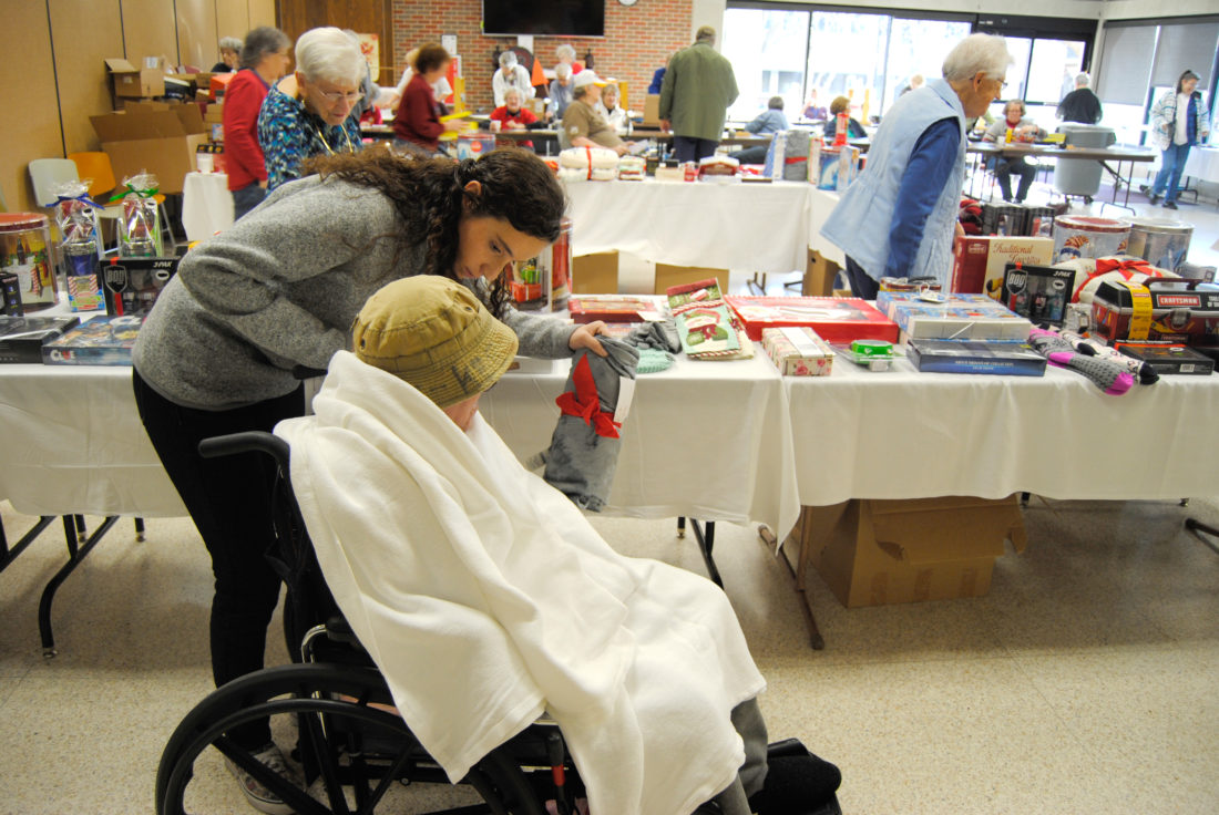 T-R PHOTO BY ADAM SODDERS West Marshall senior and National Honor Society member Rosie Dawley was one of many volunteers that escorted IVH residents during the American Legion Auxiliary Christmas Gift Wrap Tuesday.