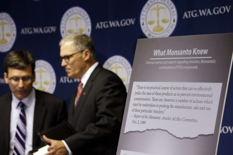 AP PHOTO Washington Attorney General Bob Ferguson, left, introduces Gov. Jay Inslee at a news conference where Ferguson announced a lawsuit against agrochemical giant Monsanto over pollution from PCBs, Thursday, in Seattle. Washington says it's the first U.S. state to sue Monsanto over pollution from PCBs.