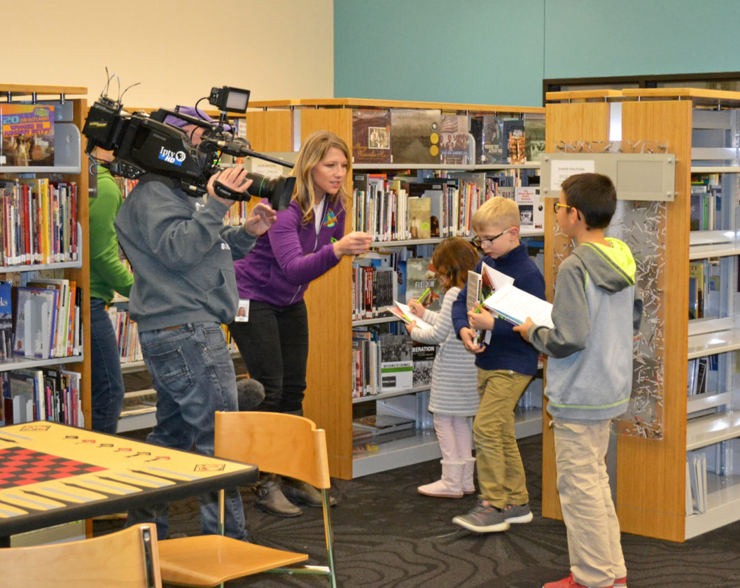"T-R PHOTO BY SARA JORDAN-HEINTZ Friday afternoon a crew from the Iowa Public Television series ""IPTV Kids Clubhouse"" came to the Marshalltown Public Library to film local children for a segment for an upcoming episode, to air in summer 2017. A total of nine youngsters participated in a filmed scavenger hunt whereby they scoured the youth department looking for a variety of reading material. Show co-host Abby Brown (center) helped encourage kids to find the items on the list."